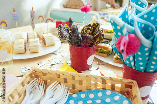 Girl birthday decorations. table setting from above with cakes, drinks and party gadgets.