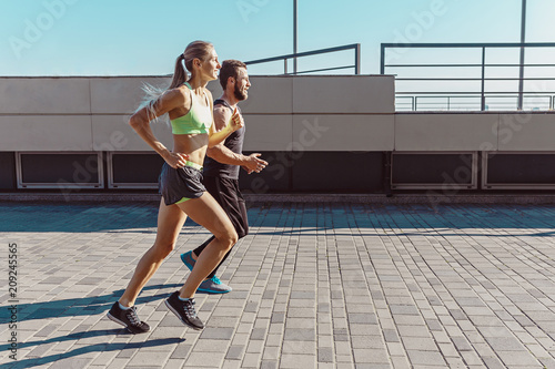 Leinwanddruck Bild Pretty sporty woman and man jogging at city