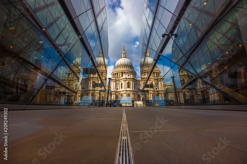 London, England - Beautiful St.Paul's Cathedral reflected in glass windows in the morning sunlight with blue sky and clouds