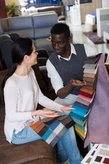 African man with his wife are choosing colors for furniture for interior their house