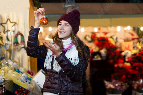Woman choosing Christmas decoration at market