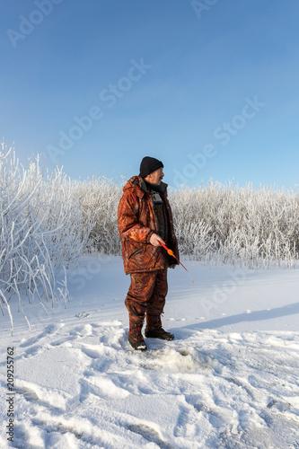 Foto Murales winter fishing. male fisherman fish in winter