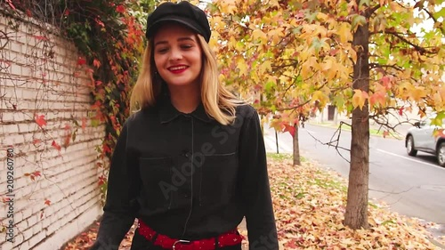 Cool urban woman walkin on the street with an autumn background
