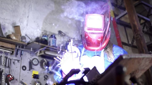 cute welder girl in uniform in the garage working with welding equipment. Women's work in art