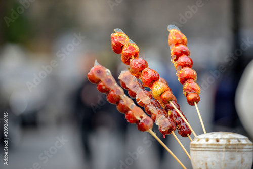 Fotobehang Peking stall with caramelized fruit on stick on street Qianmen in Beijing city. Qianmen Street runs south from Tiananmen Square, just along the Beijing central axis