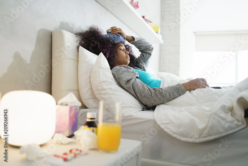Foto Murales Black Woman With Flu And Cold Holding Ice Bag