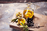 Bottle virgin olive oil and oil in a bowl with some olives - 209268326