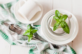 Clean glass and ceramic dishes with mint sprigs on a white wooden table. Preparing for breakfast. Soft focus. - 209269590