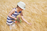 child girl walking in the yellow wheat field, bright sun, summer landscape - 209270506