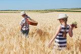 child boy and girl with guitar are in the yellow wheat field, bright sun, summer landscape - 209270514