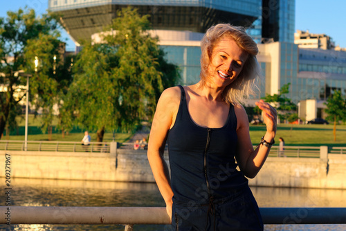 Foto Murales A girl dressed in a trendy blue overall poses on the river bank in the city. Fashion, beauty.