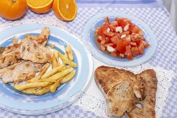 Turkey steak with french fries and tomato salad
