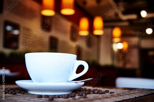 Fotobehang Koffiebonen White cup with a spoon on a saucer on a bamboo napkin with scattered coffee beans.