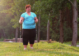 Overweight woman walking on forest trail. Slimming and active lifestyle theme.  - 209282719