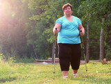 Overweight woman walking on forest trail. Slimming and active lifestyle theme.  - 209282750