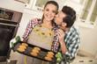 Leinwanddruck Bild - Portrait of happy young couple preparing cookies in kitchen.