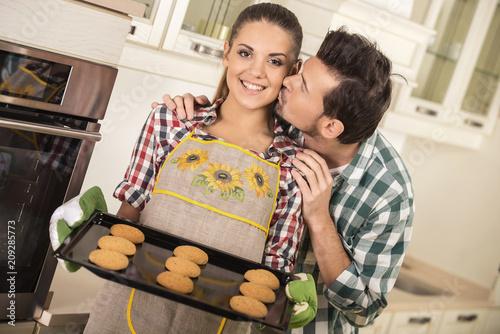 Leinwanddruck Bild Portrait of happy young couple preparing cookies in kitchen.