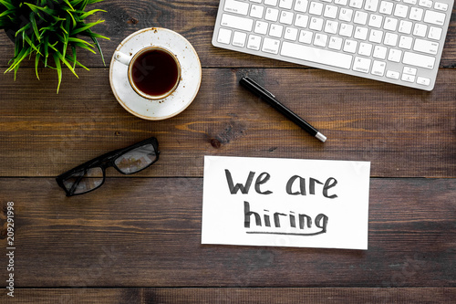 Foto Murales Search for worker, employee concept. We are hiring lettering on work desk on dark wooden background top view copy space