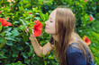 Leinwanddruck Bild - Young woman sniffing hibiscus in the park