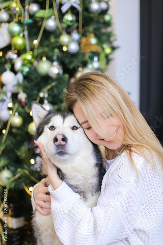 portrait of young happy girl with husky decorated fir tree in backgroundconcept of
