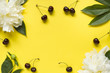 Frame from white flowers peony, Ripe cherries on a bright yellow background. Copy space