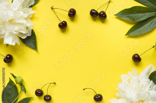 Foto Murales Frame from white flowers peony, Ripe cherries on a bright yellow background. Copy space