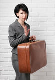 business woman dressed in a gray suit with suitcase stay in front of a white wall - 209305553