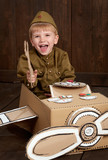 children boy are dressed as soldier in retro military uniforms repair an airplane made of cardboard box, dark wood background, retro style - 209305709