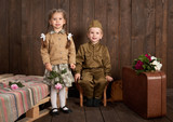 children are dressed in retro military uniforms sending a soldier to the army, dark wood background, retro style - 209305731