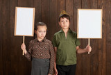 Children are dressed in retro military uniforms. They're holding blank posters for veterans portraits. - 209305746
