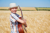 child boy with guitar is in the yellow wheat field, bright sun, summer landscape - 209305760