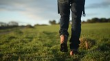 Man in hiking boots and jeans walking across a grass field. Sunrise or sunset. - 209305943