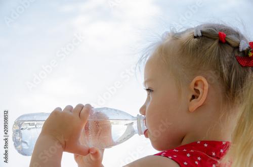 Dziecko pije wodę w upalne pragnienie gaszenia dnia