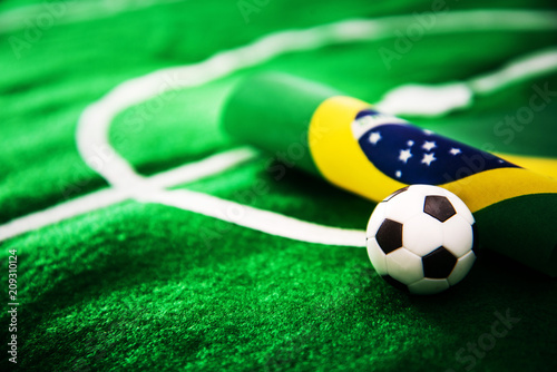 Foto Murales Brazil flag and soccer ball on green grass field