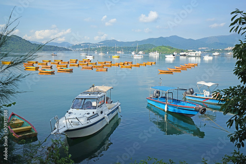 Fotobehang Zomer Yacht, fishing and recreational boats on lake and mountains