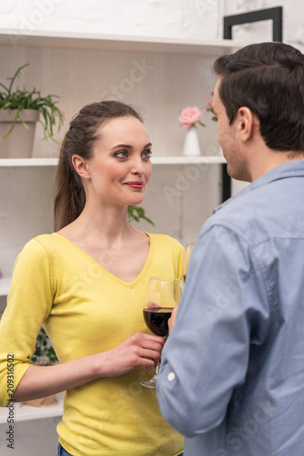 Foto Murales beautiful adult couple drinking wine and looking at each other