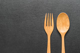 wooden  fork and spoon on black table, top view. - 209316903