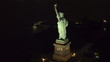 AERIAL, CLOSEUP: Famous Statue od Liberty lit up at night shining in the dark