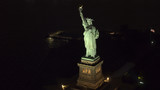 AERIAL, CLOSEUP: Famous Statue od Liberty lit up at night shining in the dark - 209317170