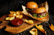 Tempting fast food diner with burgers and potatoes with sauce on cutting board
