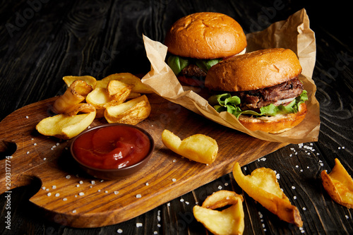 Tempting fast food diner with burgers and potatoes with sauce on cutting board - 209317774