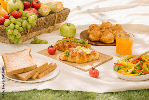Fototapeta Picnic wicker basket with food, bread, fruit and orange juice on a red and white checked cloth in the field with green nature background. Picnic concept.