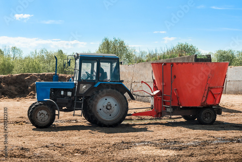 Aluminium Trekker Tractor working on farm. Blue tractor pulling red trailer. Agricultural machine
