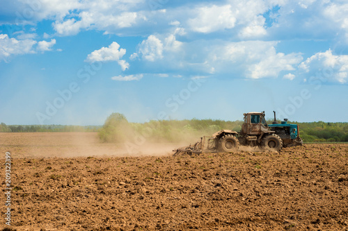 Fotobehang Trekker Tractor plowing a field on a sunny day. Preparing land for sowing. Agricultural works at farmlands. Tractor ploughing a field with a dust behind it. Agriculture industry