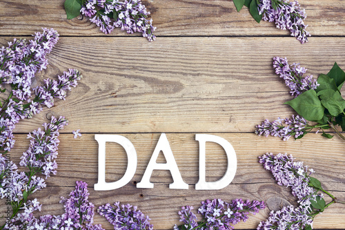 Fathers day background with letters and lilac flowers on old wooden table. Copy space. Happy fathers day concept.