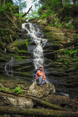 Tourist sits on a rock near a forest waterfall.