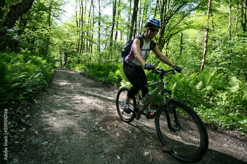 Girl on a bike riding on a forest road
