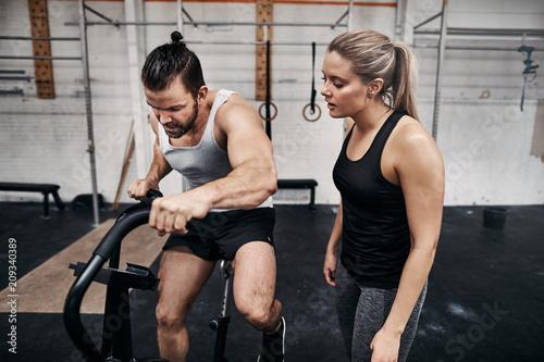 Sprawny człowiek jedzie na rowerze stacjonarnym ze swoim partnerem siłowni