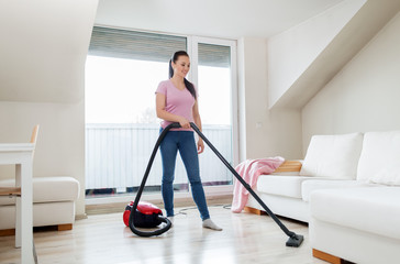 household, housework and cleaning concept - happy woman or housewife with vacuum cleaner at home