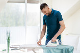 housework and household concept - man ironing shirt on iron board at home - 209341124